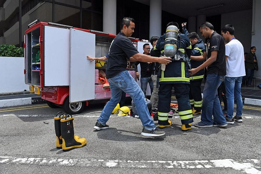 GlobalFoundries Singapore's emergency response team suiting up for the Mass Fire Evacuation Drill yesterday. The month-long campaign is aimed at promoting fire safety and emergency preparedness in commercial and industrial buildings, as well as commu