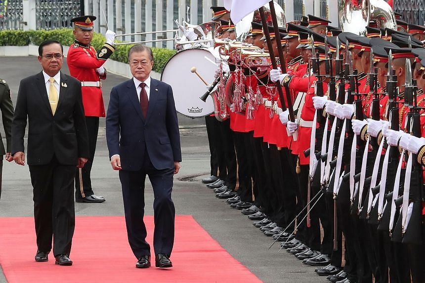 Thailand's Prime Minister Prayut Chan-o-cha and South Korean President Moon Jae-in during a ceremony at Government House in Bangkok yesterday. It is Mr Moon's first official trip to Thailand, his first stop before he visits Myanmar and Laos later thi