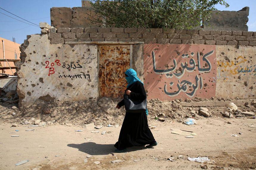 A woman walking past a shrapnel-riddled wall in Iraq's Baiji in 2014.