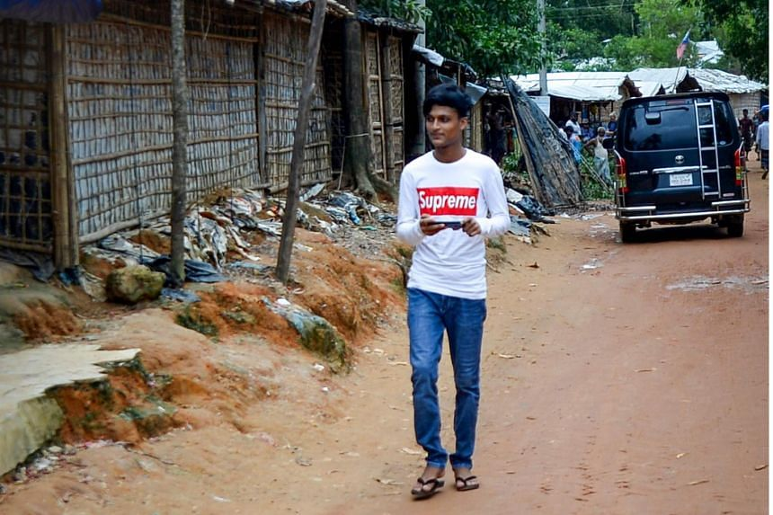 In a picture taken on July 23, 2019, a Rohingya youth walks around the Kutupalong refugee camp in Bangladesh with his mobile phone. Telecommunications operators have seven days to submit reports on the actions they have taken to shut down networks in