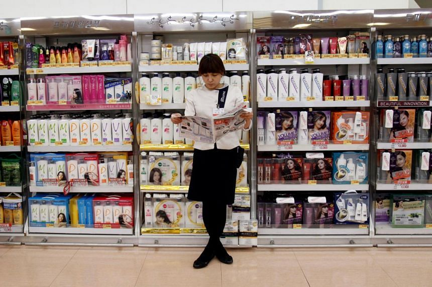 A saleswoman reads a newspaper as she waits for customers in front of hair products at a supermarket, in Seoul.