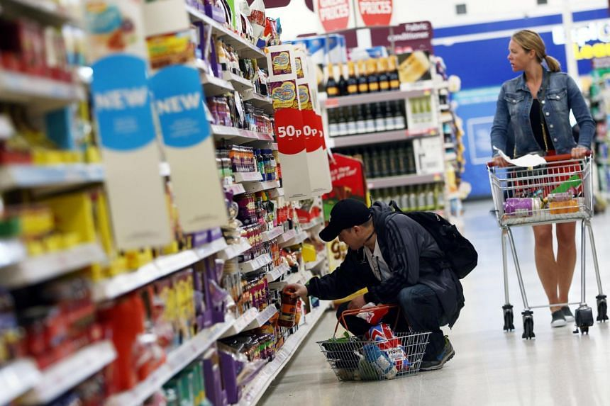 Shoppers browsing food aisles in a supermarket in London, Britain, on April 11, 2017.