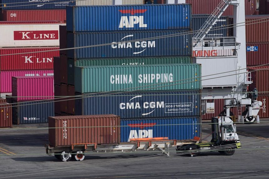 A truck passes by shipping containers at the Port of Los Angeles in Long Beach, California, on Sept 1, 2019.