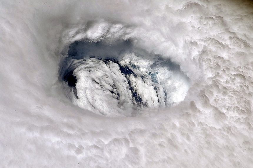 An image of Hurricane Dorian's eye taken by a Nasa astronaut from the International Space Station on Monday. Waves splashing against the shoreline in Titusville in the US state of Florida on Monday. Hurricane Dorian was expected to approach the Flori