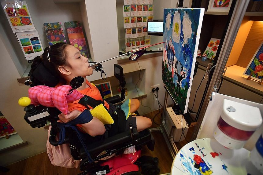 Ms Elaine Eng, who loves to paint, using the E-Canvas device that works by voice command. The 19-year-old, who has spastic-dystonic quadriplegia and is unable to use her arms, legs and body, paints by wielding a brush in her mouth. ST PHOTO: LIM YAOH