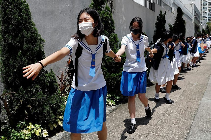 Secondary school students in Hong Kong joining hands to form a human chain as they boycotted classes for a second day and joined pro-democracy rallies. PHOTO: REUTERS People participating in a protest rally at Tamar Park in front of government buildi