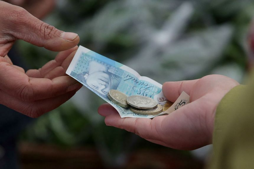 A trader passes a customer their change in the form of a five pound sterling note and one and two pound coins.