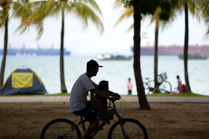 A father cycling with his child at a park in Singapore.