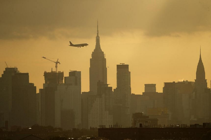A plane due to land at LaGuardia Airport passes the New York City skyline, on Aug 26, 2019.