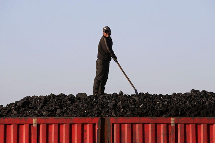 In this picture taken on Oct 24, 2015, a worker loads coal on a truck at a depot near a coal mine on the outskirts of Jixi, in Heilongjiang province, China.