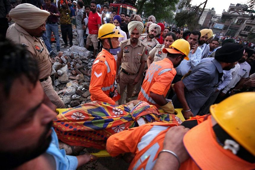 National Disaster Response Force personnel bring out a body from the rubble as rescue work continues.