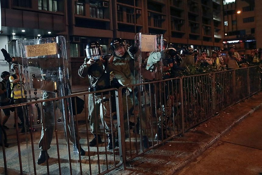 """Police officers outside Mongkok police station last night. Over 100 protesters gathered there, chanting """"five core demands, not one less"""", after Hong Kong leader Carrie Lam announced the withdrawal of the extradition Bill."""