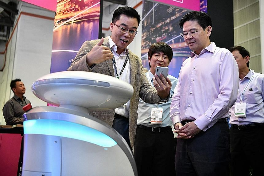 National Development Minister Lawrence Wong viewing a cleaning robot, Ava, at the LionsBot booth yesterday at the International Built Environment Week, which is being held at integrated resort Marina Bay Sands' Sands Expo and Convention Centre.