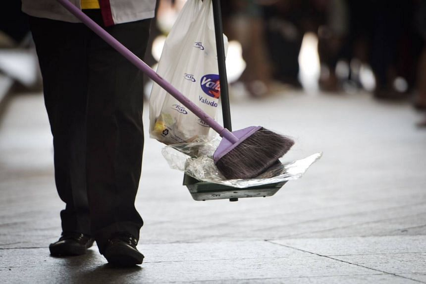 A cleaner sweeping up rubbish on a pavement in Oct 2018.