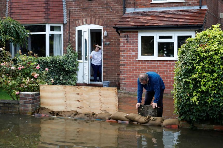 A man tries to prevent rising flood water from entering his house in Manchester, Britain, on July 31, 2019.