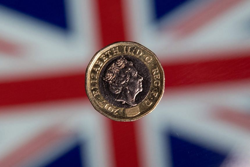 A British one pound sterling coin is arranged for a photograph in front of a Union flag in London.