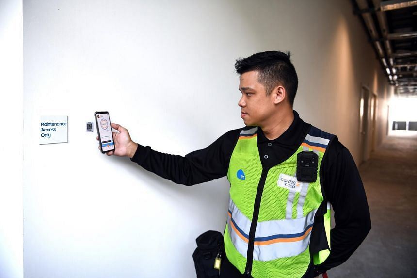 "A security officer uses smart mobile app ""Argus"" to send location reporting data at the JTC Space@Tuas building. The app is part of Certis' offerings under its new contract with JTC."