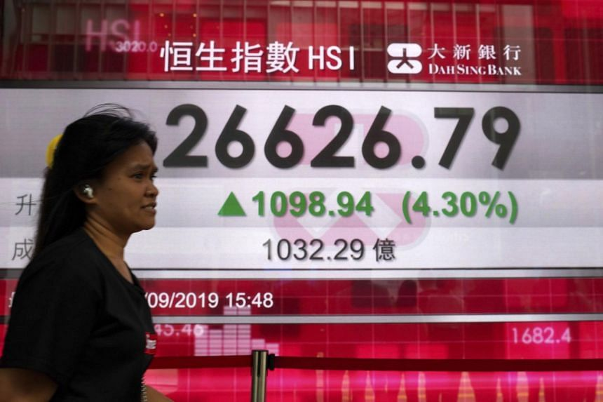A woman walks past an electronic board showing Hong Kong share index outside a local bank in Hong Kong, on Sept 4, 2019.