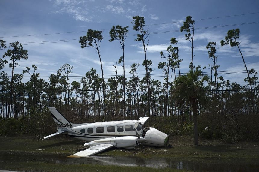 A plane sits on the side of a road in the Pine Bay neighborhood, in Freeport, Bahamas.