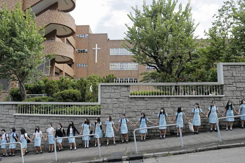 Students in blue school dresses held hands on Friday (Sept 6) outside Maryknoll Convent School, a Catholic girls' school.