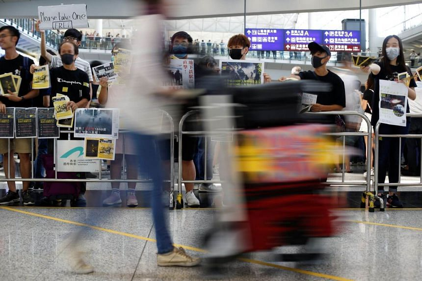 Anti-extradition Bill protesters holding up placards for arriving travellers at Hong Kong International Airport, on Aug 9, 2019.
