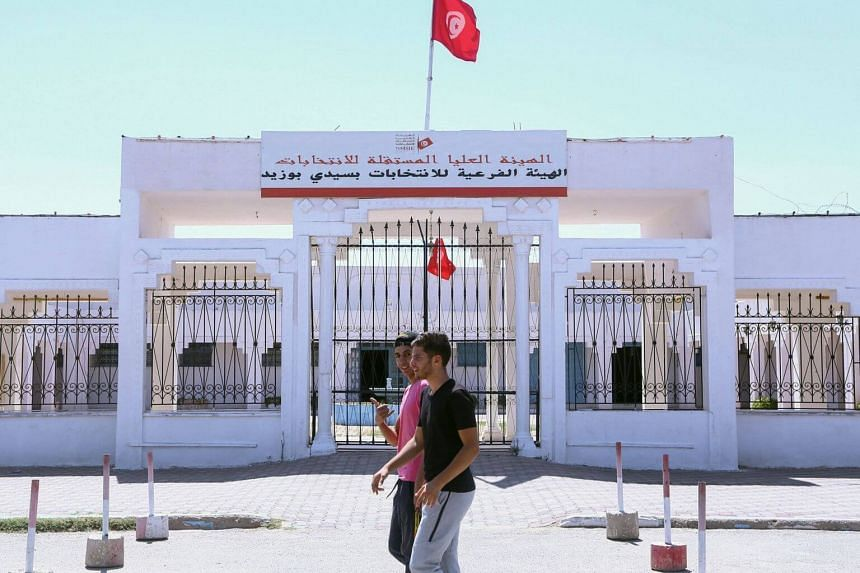 Tunisian youths walk past a branch of the Independent High Authority for Elections on Aug 15, 2019.