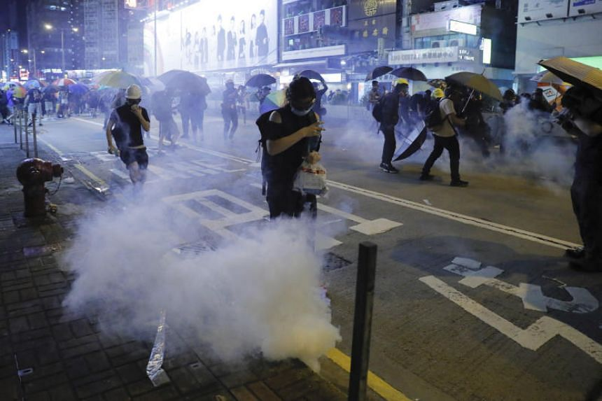 Protesters run for cover from tear gas shells during a protest in Mong Kok, Hong Kong on Sept 6, 2019.