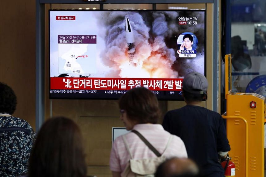 In a photo taken on Aug 24, 2019, people watch breaking news of North Korea's projectile launch at Seoul Station in South Korea.