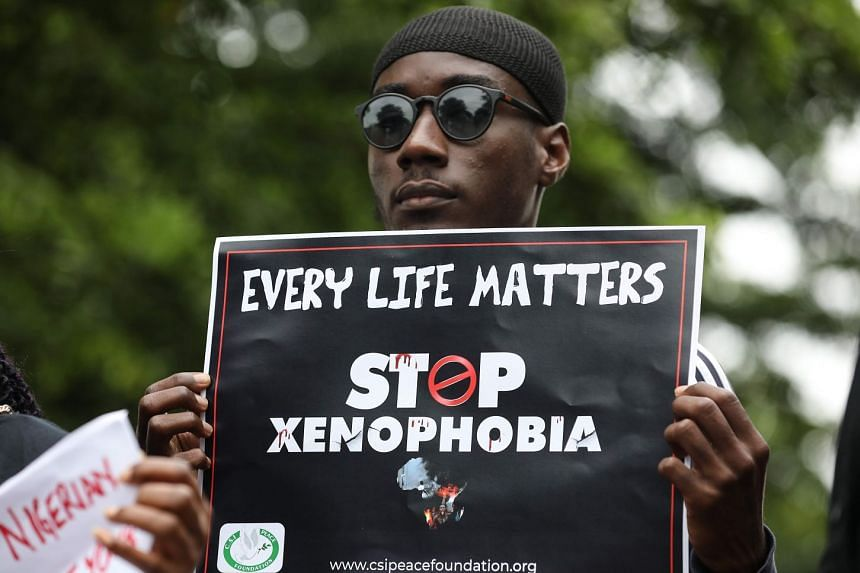 A demonstrator holds a sign during a protest against xenophobia outside the South African High Commission in Abuja