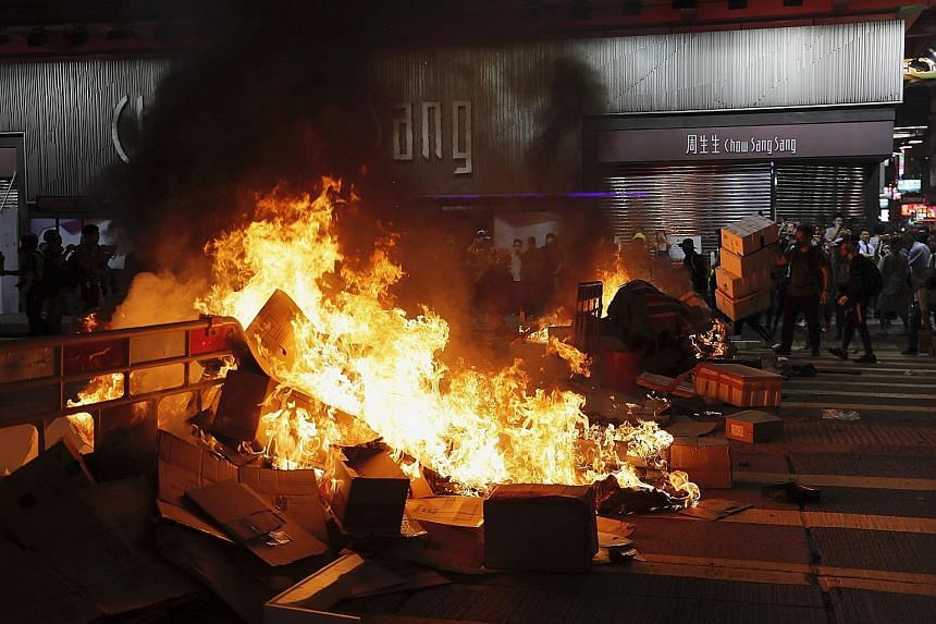Protesters standing next to a burning barricade they set up during a protest in Mong Kok last night. Police fired tear gas and rubber bullets to disperse the crowd. PHOTO: ASSOCIATED PRESS
