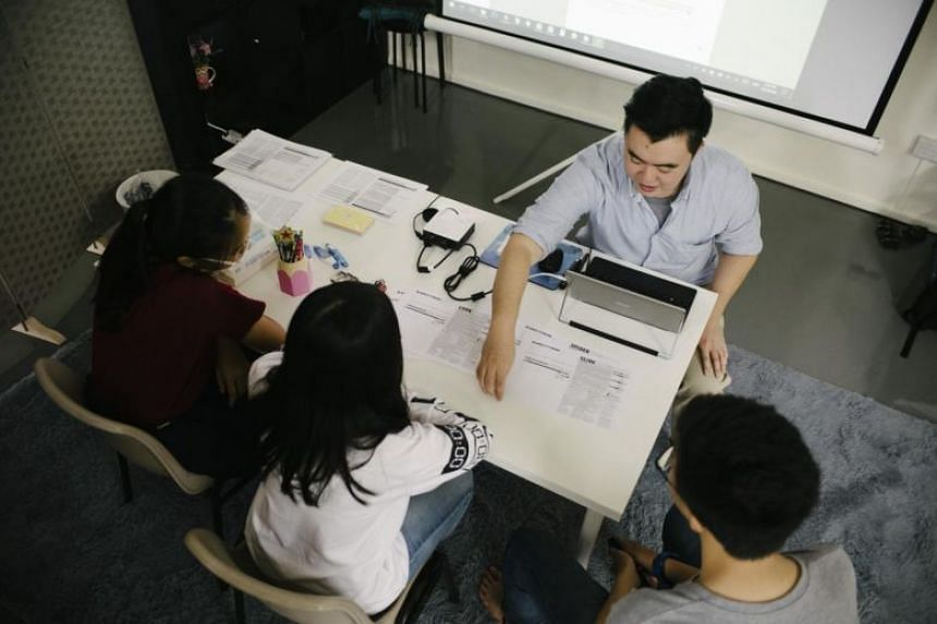 A file photo taken on March 6, 2018, showing a tutor interacting with students. Higher spending on private tuition was a key contributor to an uptick in educational expenses last year.