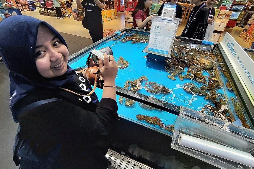 Ms Utari Octavianty at Freshippo, Alibaba's robot-driven supermarket, in Hangzhou, on Aug 28, under the Tech for Inclusion workshop. She is interested in the seafood supply chain as she is the co-founder of Aruna, an Indonesian fisheries e-commerce start-