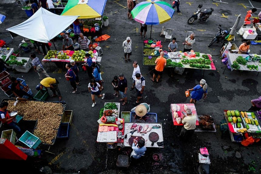 People buying vegetables at a market in Bentong, outside Kuala Lumpur in the nearby Pahang state, on Sept 4, 2019.