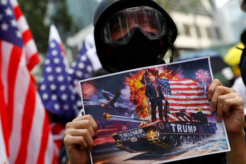 A protester holds up a sign featuring US President Donald Trump in a tank, in Central, Hong Kong, on Sept 8, 2019.