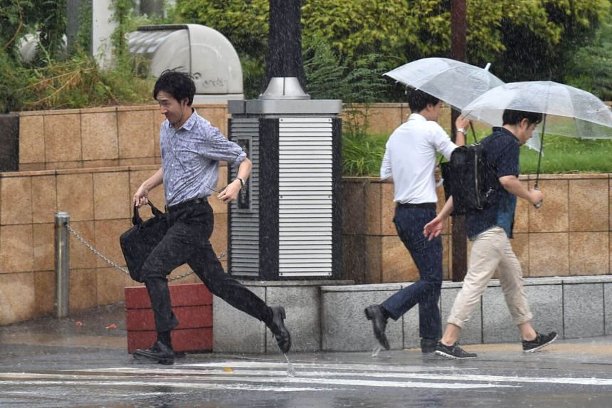Pedestrians walking under heavy rain in Tokyo, on Aug 15, 2019. Typhoon Faxai is forecast to reach coastal areas near Tokyo in the late hours of Sunday (Sept 8).