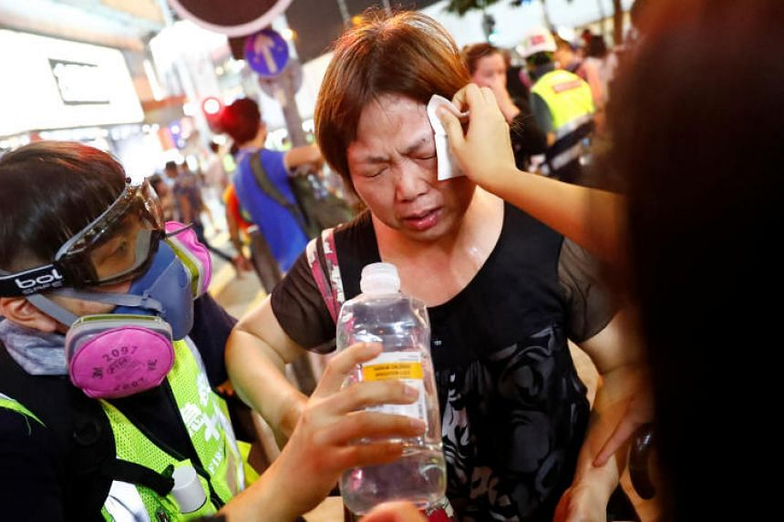 A woman receives water after riot police fired tear gas outside the Causeway Bay MTR station on Sept 8, 2019.