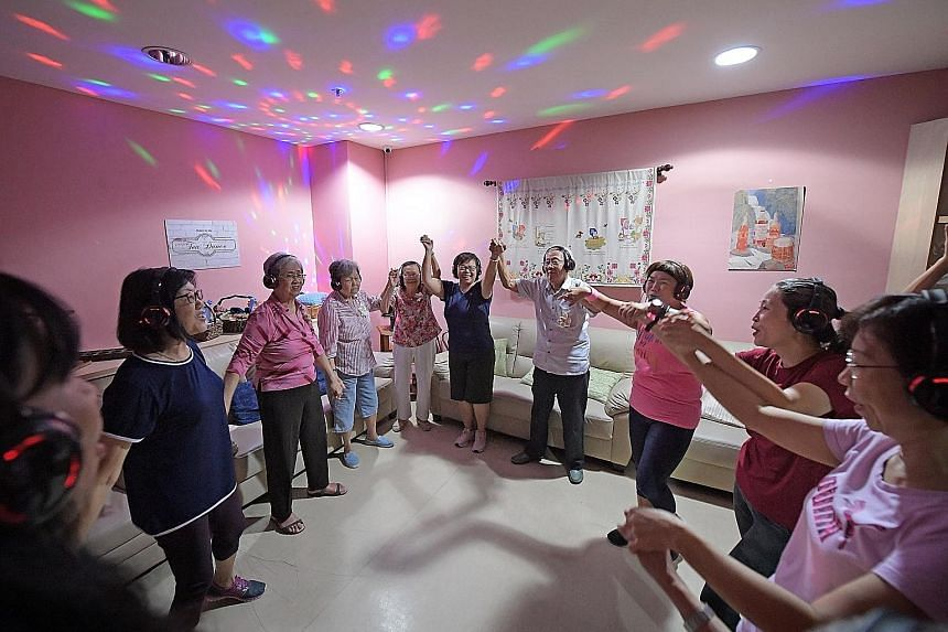 A silent disco session being led by facilitator Karrayl Sim (third from right) at Alzheimer's Disease Association's New Horizon Centre in Jurong Point last Wednesday. Among the participants were Madam Lily Goh (third from left), as well as husband-an