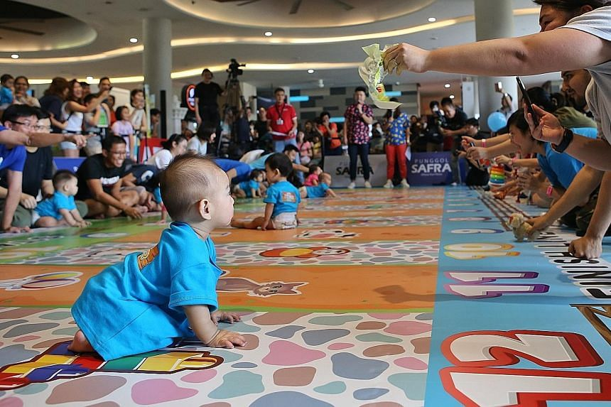 """Parents cheering their babies on as they took part in a """"diaper dash"""" competition yesterday at the My Family Fiesta event at Safra Punggol. PHOTO: LIANHE ZAOBAO"""