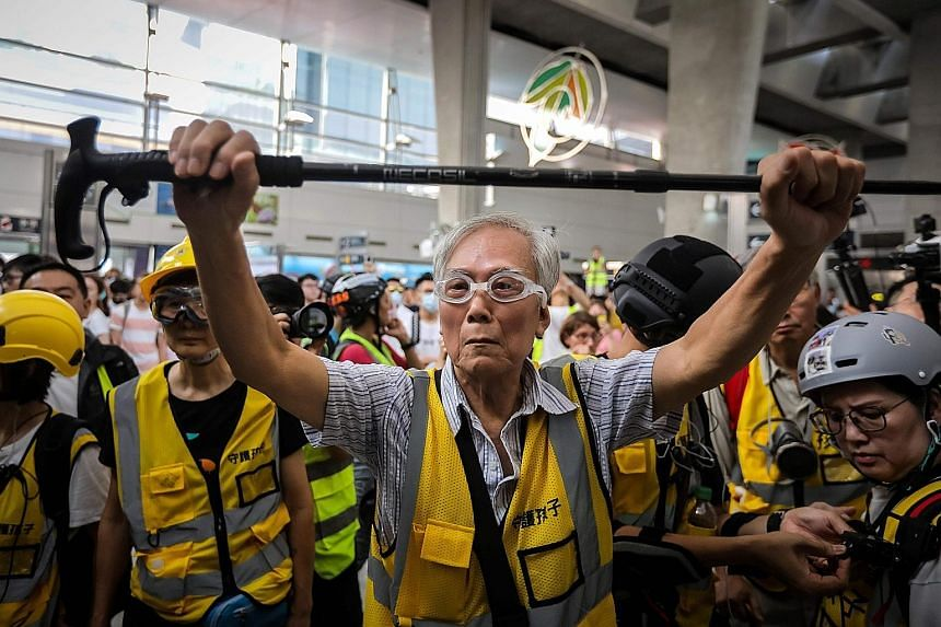 "An 85-year-old volunteer, known as Grandpa Wong, holding up his walking stick to shield protesters from the police, along with other ""silver hair"" volunteers in Hong Kong's Tung Chung district last Saturday. They are part of a group called Protect th"