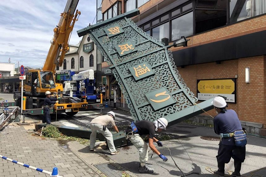 Workers take out a destroyed shopping street gate following strong wind generated by Typhoon Faxai on a highway in Kamakura, Kanagawa prefecture, near Tokyo, Japan, on Sept 9, 2019.