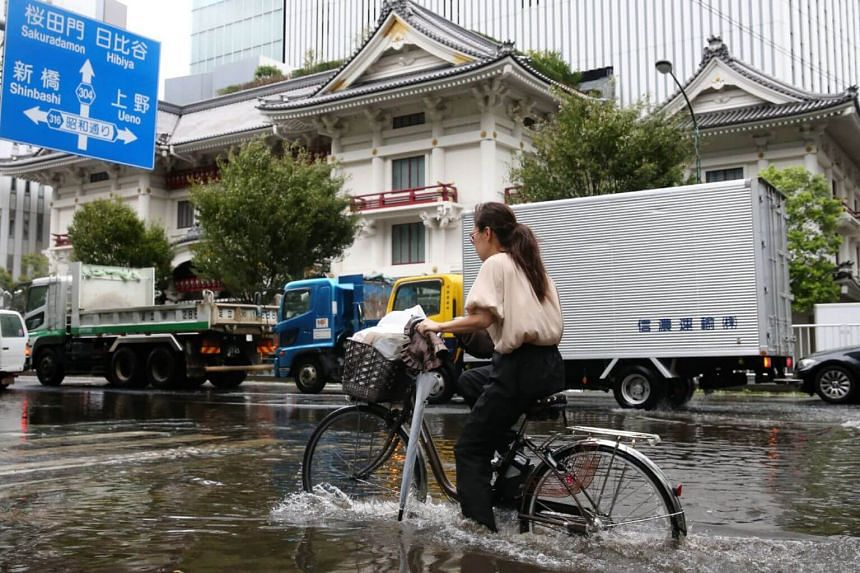 A woman cycles through a flooded area in Tokyo, on Sept 9, 2019.