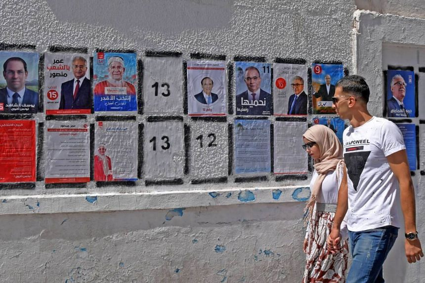 Tunisians walk in front of posters of presidential candidates in the capital Tunis, on Sept 7, 2019.