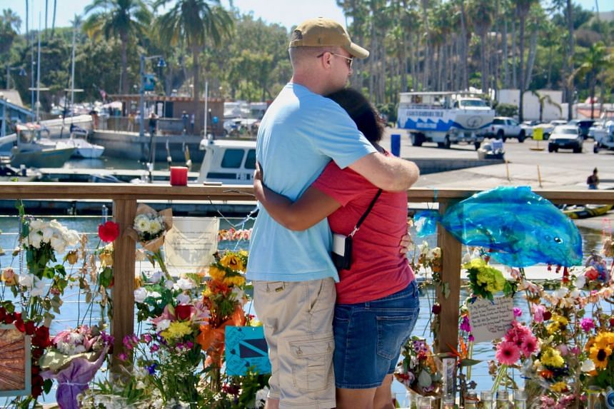A couple stand next to a memorial at Santa Barbara Harbour.