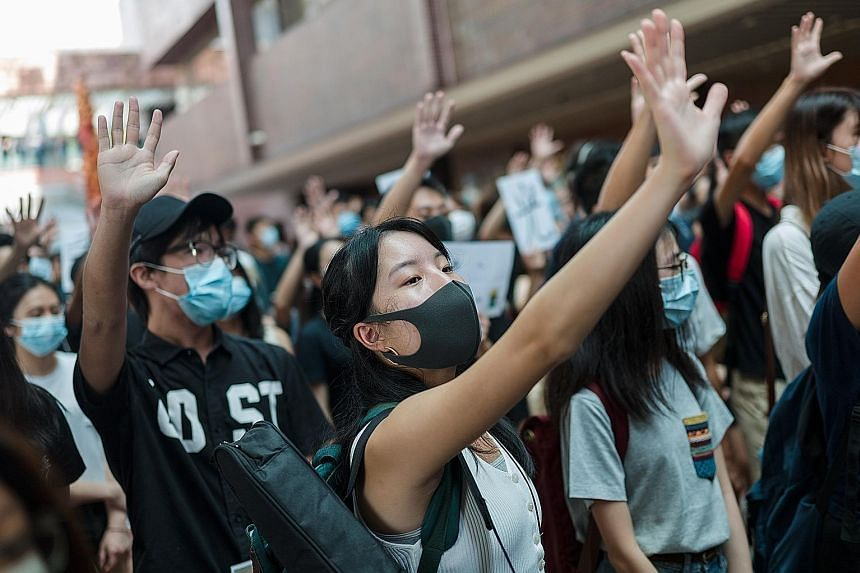 Left: Students from the City University of Hong Kong and Hong Kong Baptist University linking hands to form a human chain yesterday. Below: Students at a rally at the University of Hong Kong yesterday. They are indicating that they want all five of t