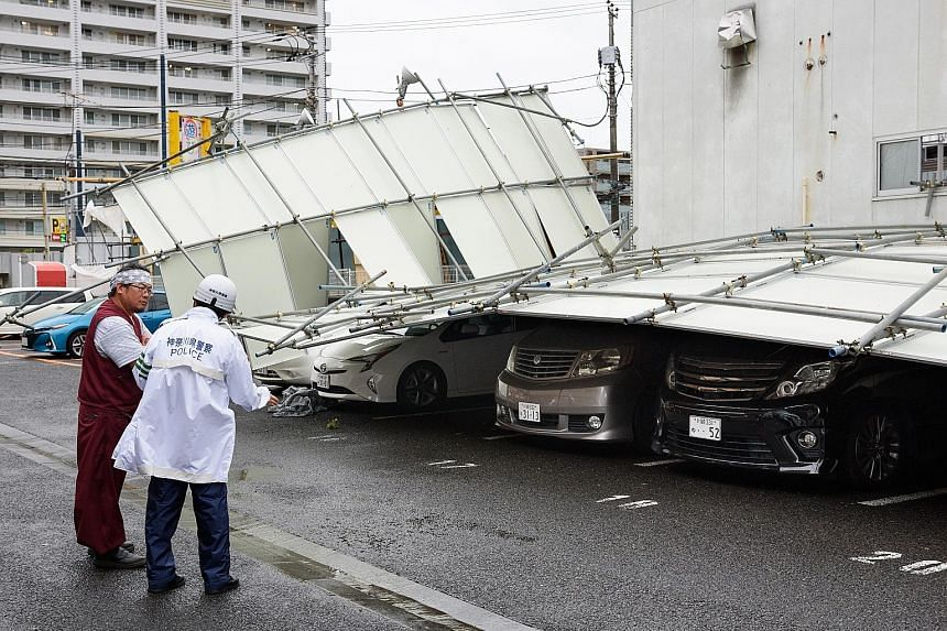 A fence blown over by strong winds in Kawasaki, Kanagawa prefecture, yesterday. Among those killed was a woman in her 50s in Tokyo, who died after she was smashed against a building by strong gusts, according to security camera footage. PHOTO: BLOOMB