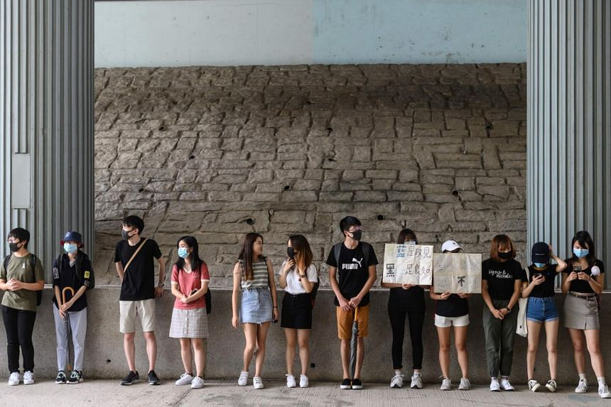 """Students of Baptist University and City University take part in a joint university """"human chain"""" rally to highlight the five demands protesters are asking from the government, in the Kowloon Tong district in Hong Kong on Sept 9, 2019."""
