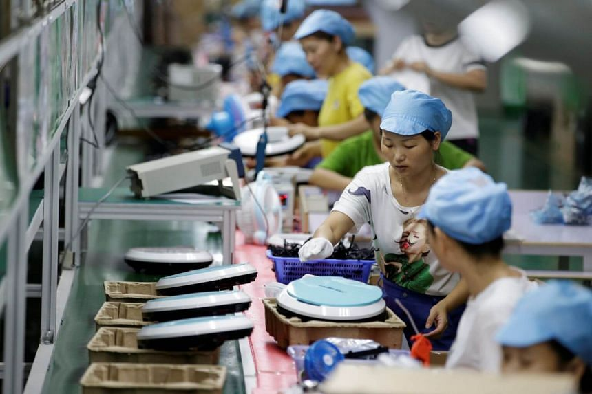 Employees work on the production line of a robot vacuum cleaner factory of Matsutek in Shenzhen, China.