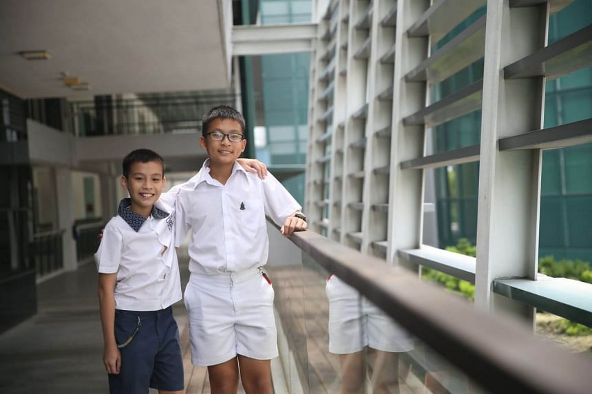 Raffles Institution year one student Joash Lim (right), and his younger brother Joarim, a Primary 5 student at St. Hilda's Primary School, have both received the Raffles Scholarship.