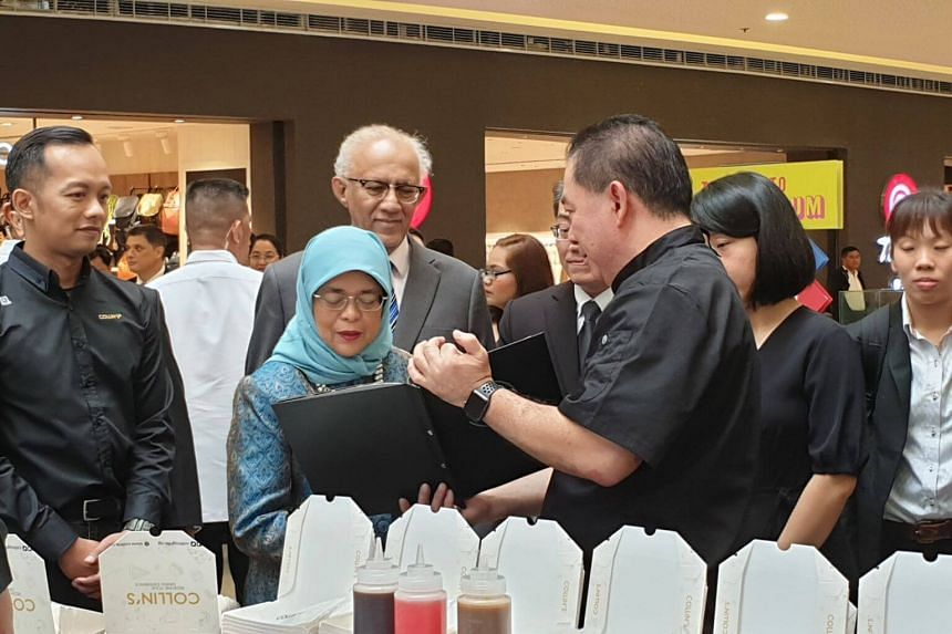 President Halimah Yacob interacts with staff from Collin's, a Singapore food and beverage chain that is exhibiting its products at Singaporium, a consumer and lifestyle pop-up in Manila.