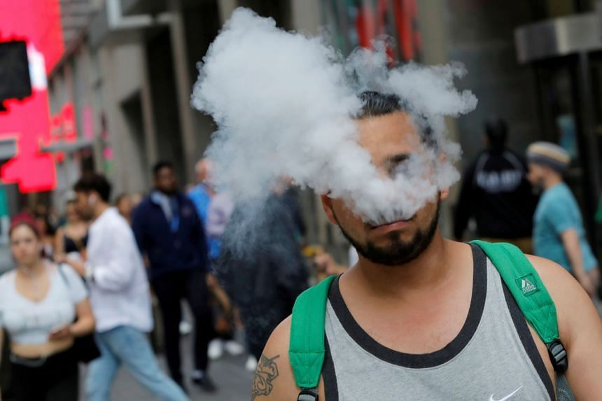 """A man """"vapes"""" as he walks on Broadway in New York City."""